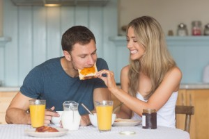 Cute couple having breakfast together at home in the kitchen